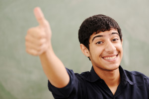 Male teenager student in front of classroom board showing thumb up, college, young pupil at university